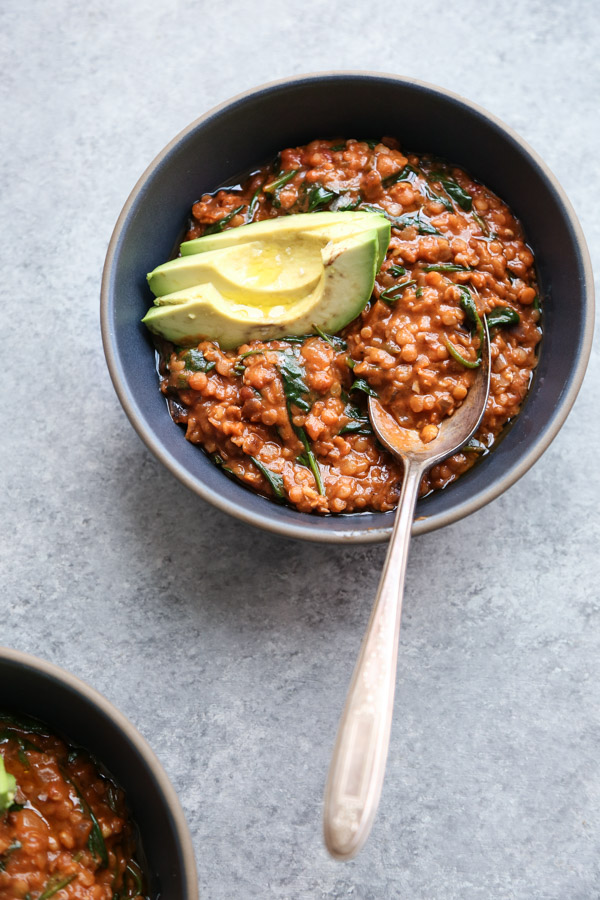 Red lentil curry with spinach in a bowl with spoon