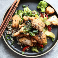 Sesame Chicken with Broccoli and Red Peppers on a black plate