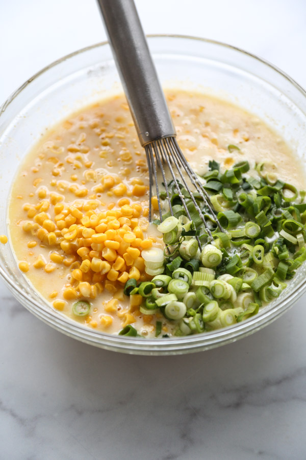 corn and scallions in a mixing bowl