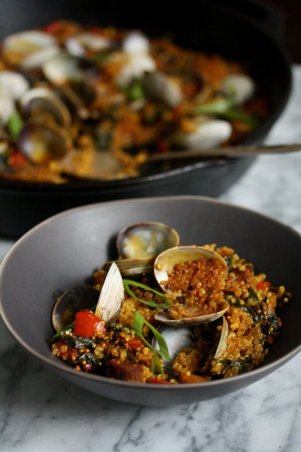 An easy quinoa paella with spicy chorizo sausage, seafood, peppers and winter greens. It's a great healthy spin on classic Spanish paella.