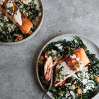 Seared Salmon on a plate with kale, chickpeas, quinoa and sauce
