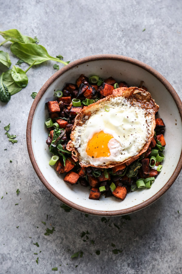 sweet potato black bean hash in a bowl with fried egg