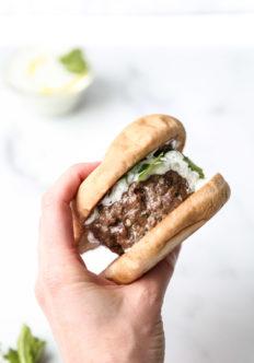 holding greek lamb burger in gluten-free bun