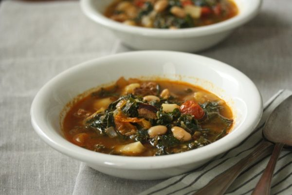 This healthy authentic Portuguese kale soup recipe uses smoked linguica, potatoes, beans and cherry tomatoes