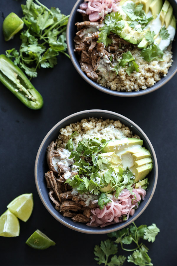 The quick pulled pork for this healthy burrito bowl recipe is a quick sweet and sour spin on Mexican carnitas. It's perfect with quinoa, avocado, pickled shallots and kefir jalapeno crema! | Feed Me Phoebe