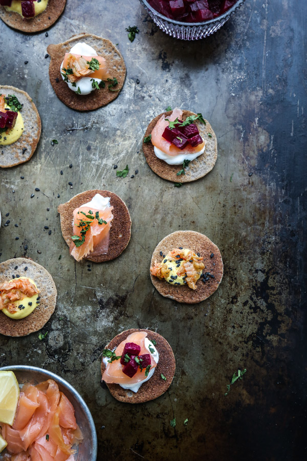 This buckwheat blini recipe is an easy, healthy spin on the traditional pancake, but tastes just as delicious! Serve to your gluten-free dairy-free friends! Top them with smoked salmon, beets, Greek yogurt and/or chopped kimchi