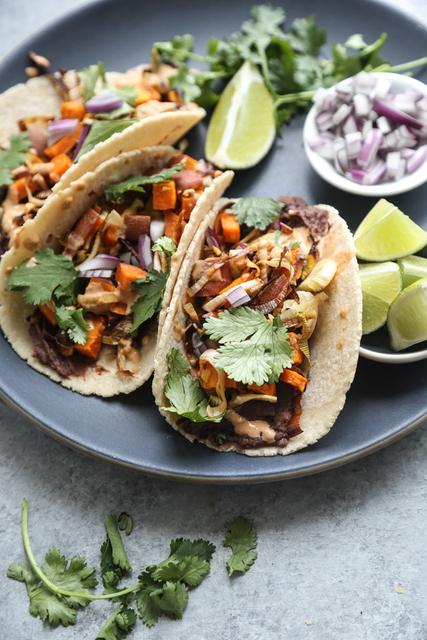 These vegetarian black bean tacos are made with chile-spiked refried beans, roasted sweet potato- leek hash, and spicy chipotle tahini sauce. Easy + delish! | Feed Me Phoebe