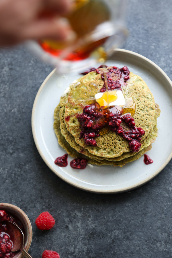 stack of green pancakes with raspberries on a plate