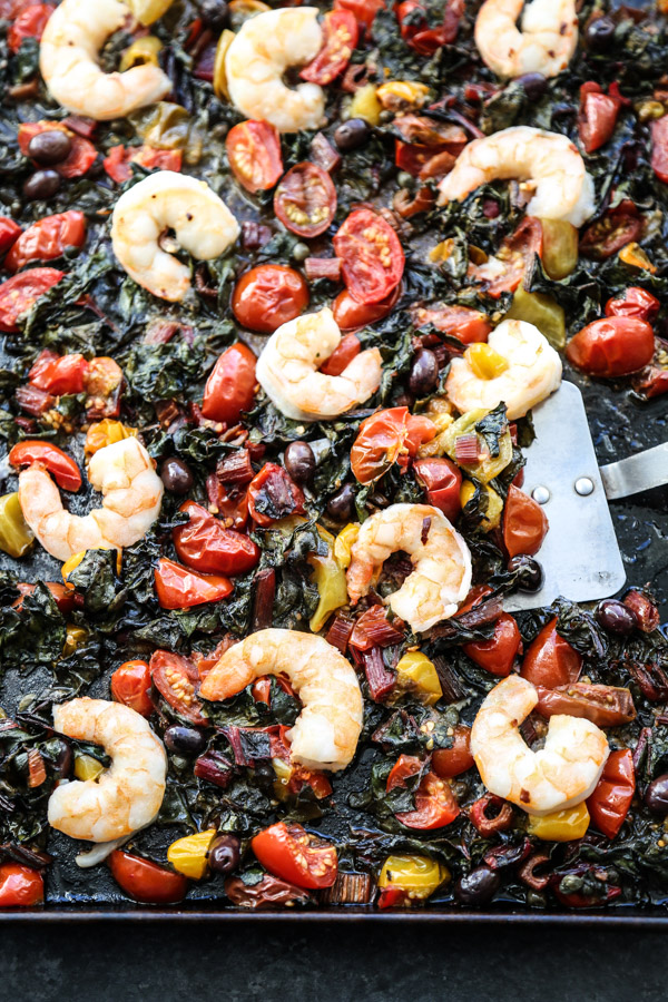 A sheet pan full of shrimp, cherry tomatoes, chard, puttanesca sauce.