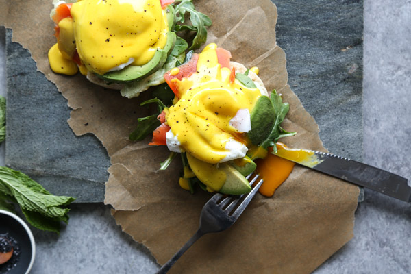 English muffin with salmon and avocado on a serving tray with herbs, eggs hollandaise and salmon