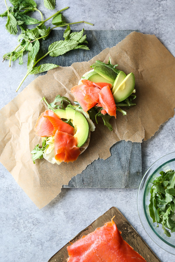English muffin with salmon and avocado on a serving tray with herbs