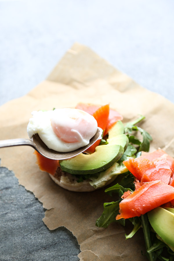 English muffin with salmon and avocado on a serving tray with herbs, eggs and salmon