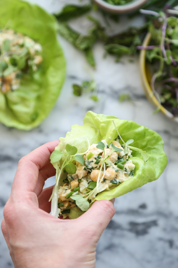 chickpea salad in a lettuce cup wrap in hand