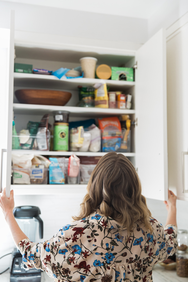 girl opening cabinets with pantry organizers