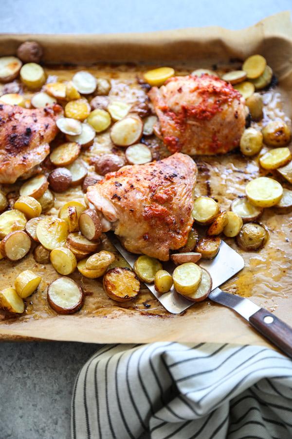 spatula holding peri peri chicken and potatoes on a sheet pan