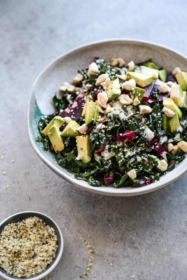 kale salad with avocado in a bowl with hemp seeds