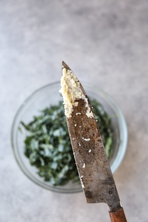 garlic paste on a knife over a bowl of kale