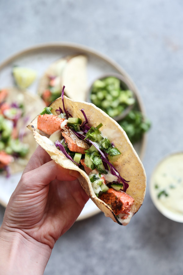 hand holding salmon fish tacos