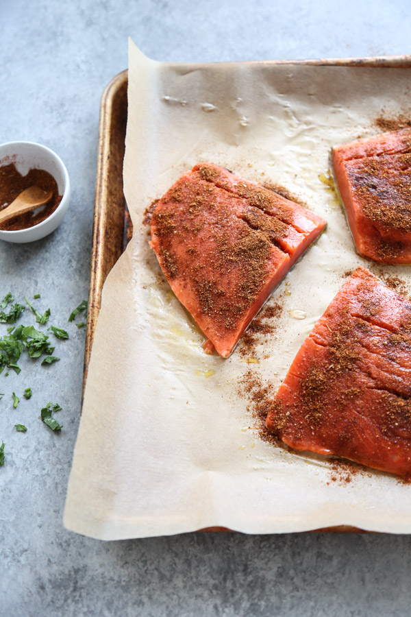 salmon on a sheet pan with parchment paper sprinkled with taco seasoning