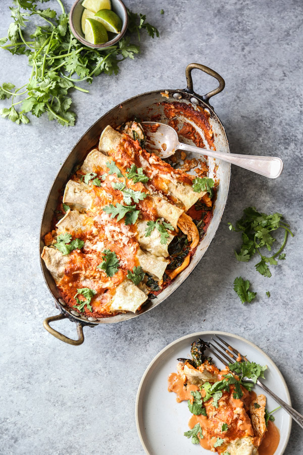 chicken enchiladas in a casserole dish with red sauce