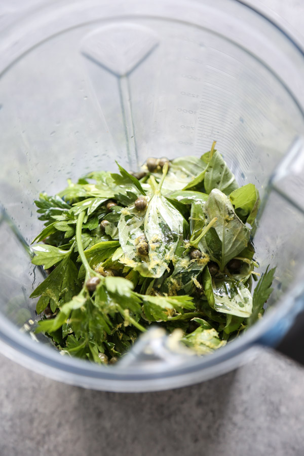 herbs in a blender with capers