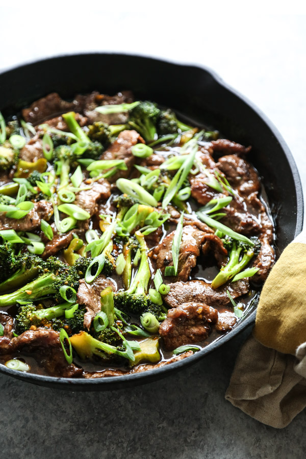 mongolian beef in a skillet with spatula and scallions