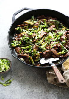 mongolian beef in a wok with spatula and scallions