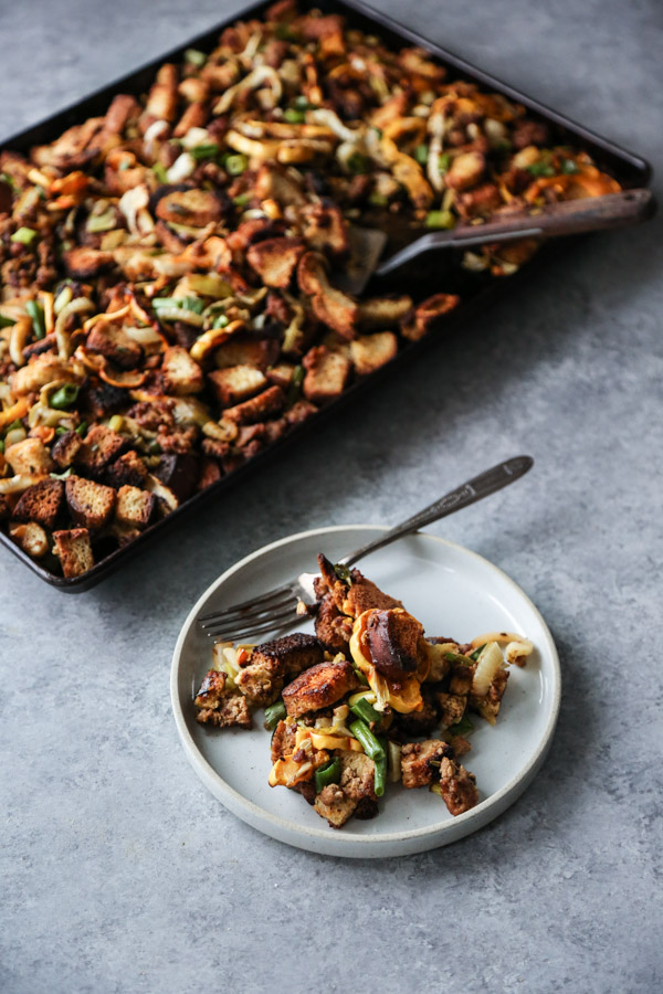 sheet pan thanksgiving stuffing with spatula and stuffing on a plate