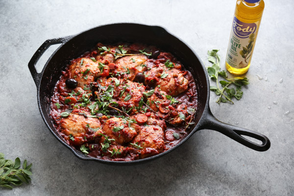 chicken cacciatore in a skillet with oregano and parsley