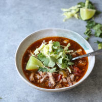 pozole rojo recipe in a bowl with cilantro and lime