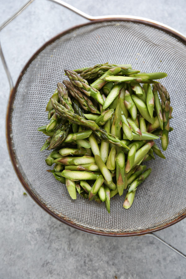 uncooked asparagus in a sieve