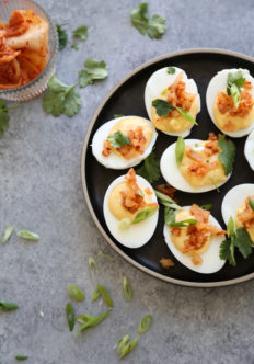 deviled eggs on a plate with herbs