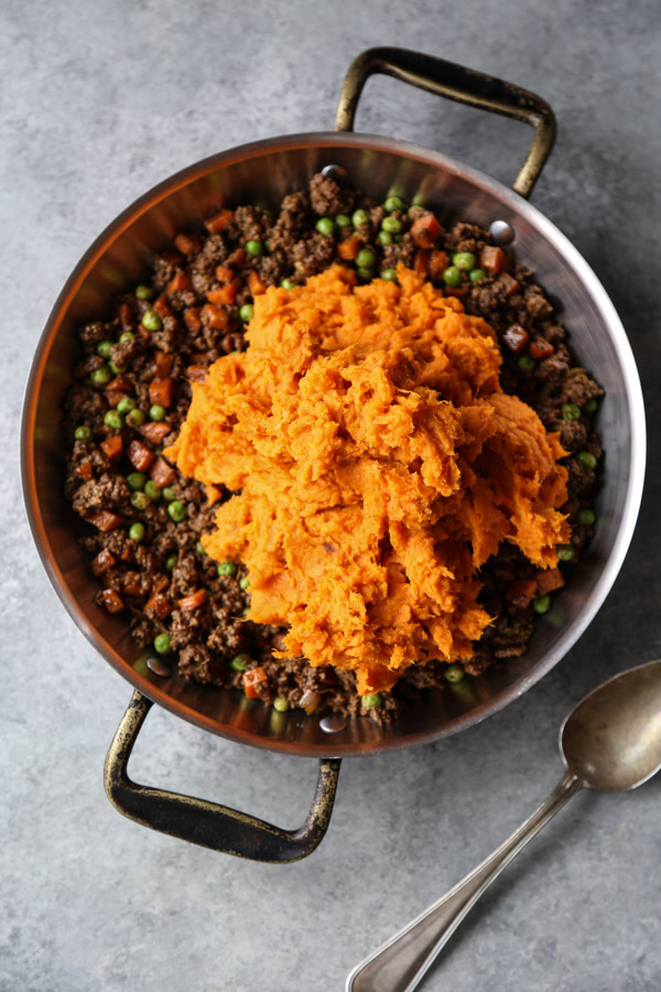 ground lamb shepherd's pie in a casserole pan with sweet potato mash