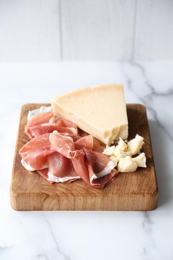 prosciutto and gana padano on a cutting board