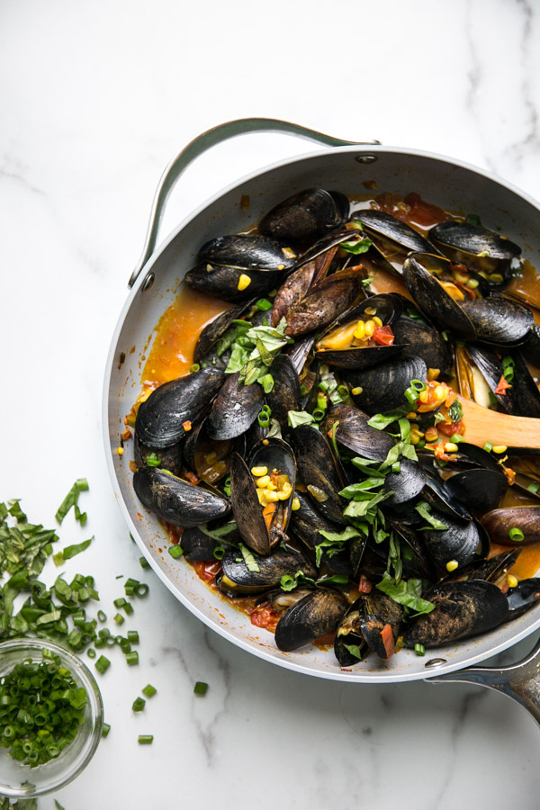 Mussels with red sauce and corn in a pan